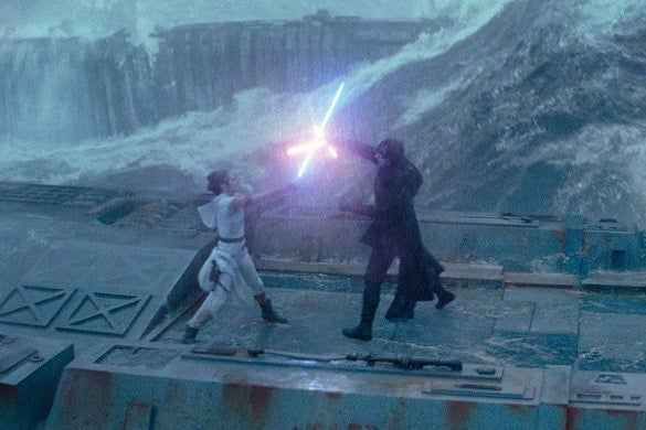 Rey and Kylo Ren fight with lightsabers atop a metal structure surrounded by waves.