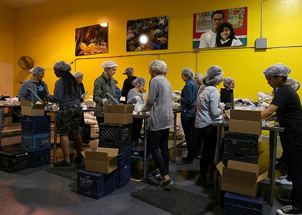 Volunteers pack bags of rice at the San Francisco Food Bank.