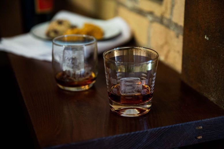 Two glasses of brown-colored Cynar on a dark wood panel
