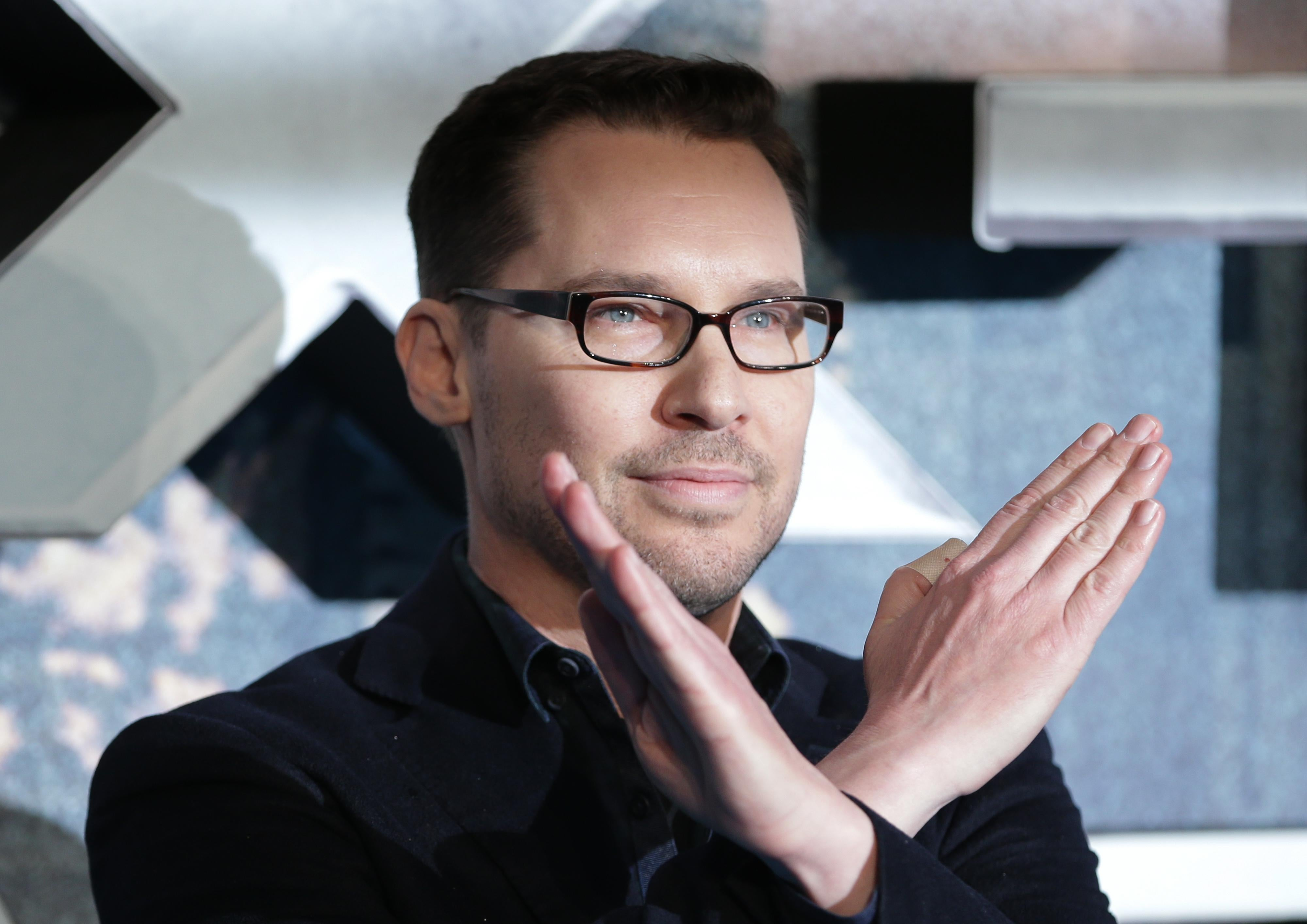 Bryan Singer with his arms in the shape of a letter X, crossed at the wrists.