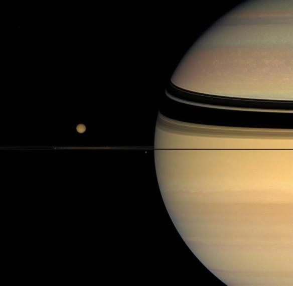 Four moons huddle near Saturn's multihued disk.