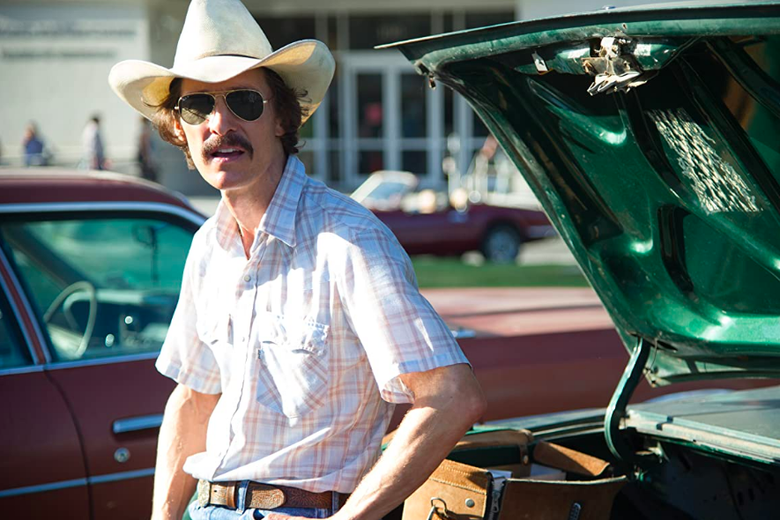 Matthew McConaughey leans against a car wearing a cowboy hat and a thick handlebar mustache.