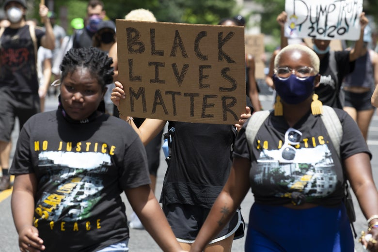 Two demonstrators hold hands amid a Black Lives Matter march