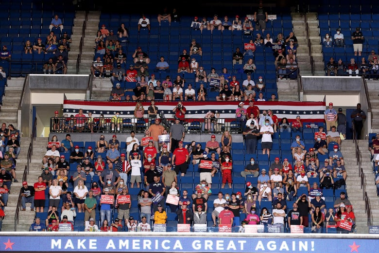 Trump supporters sit in the stands. There are many empty seats.