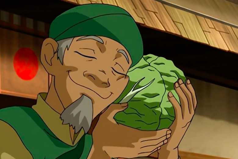 A cartoon man with a green cap and a gray beard lovingly cradles a head of cabbage against his cheek.
