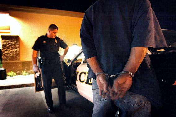 Tucson Police Officer Angel Ramirez arrests a man for trespassing May 29, 2010 in Tucson, Arizona.