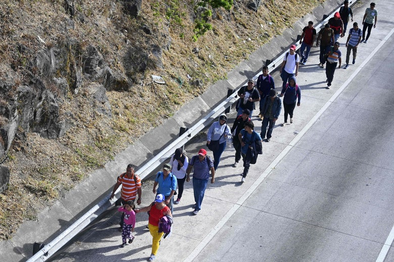A group of Salvadoran migrants walking on a road.