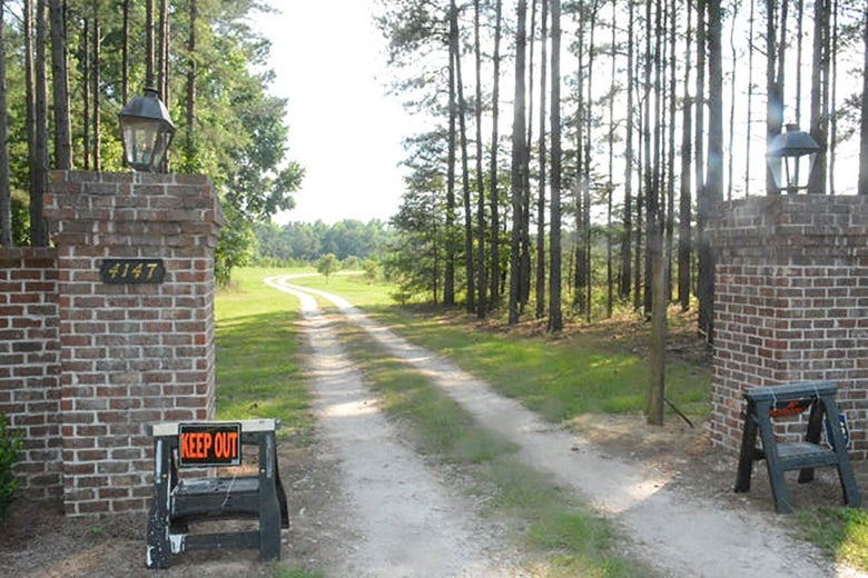 Two sawhorses bearing KEEP OUT signs are seen in front of a brick gate, through which a dirt road is seen.