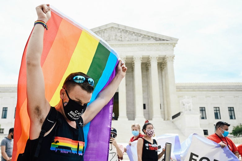 Person holding up a rainbow flag in front of the Supreme Court building