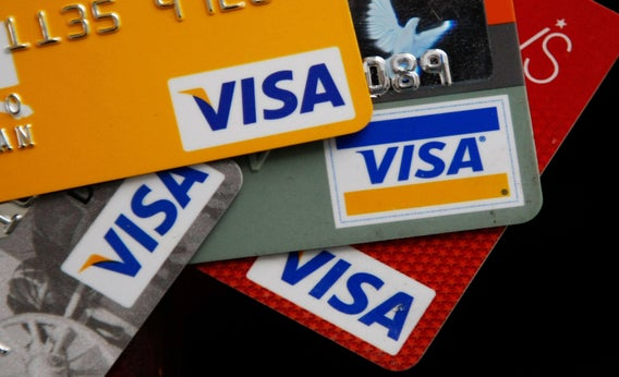 A coffee shop displays signs for Visa, MasterCard and Discover.