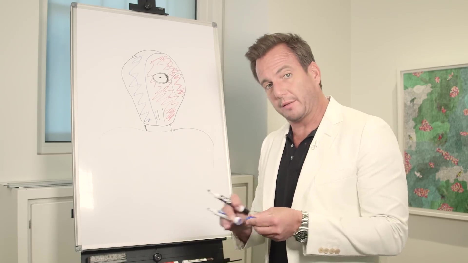 Will Arnett stands in front of a not-very-convincing drawing of Slade.