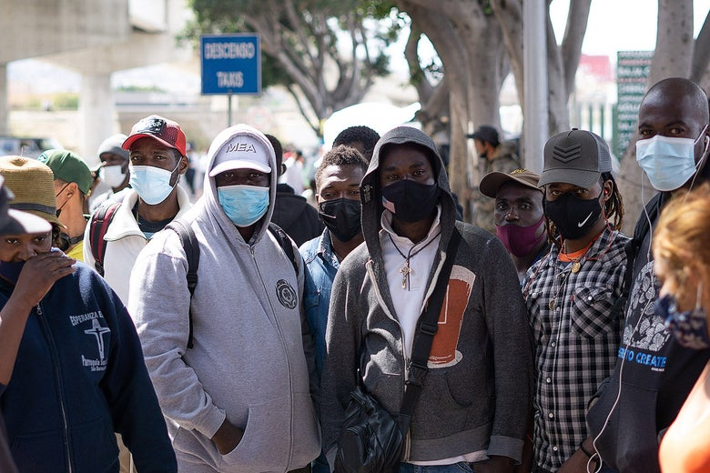 A group of men stand together wearing masks.