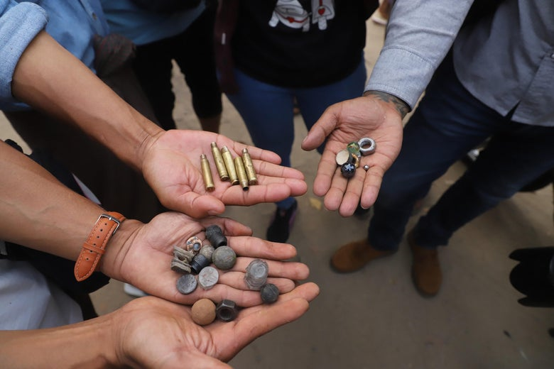Protesters hold out bullet cartridges and ammunition for slingshots after security forces fired on demonstrators at a rally against the military coup in Mandalay on February 20, 2021.