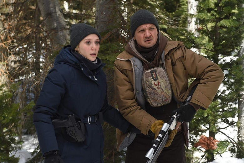 Man and woman standing in the woods. Man is holding a rifle.