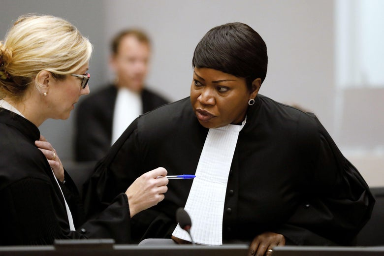 Fatou Bensouda speaks to a woman who is gesticulating with a pen near a microphone.