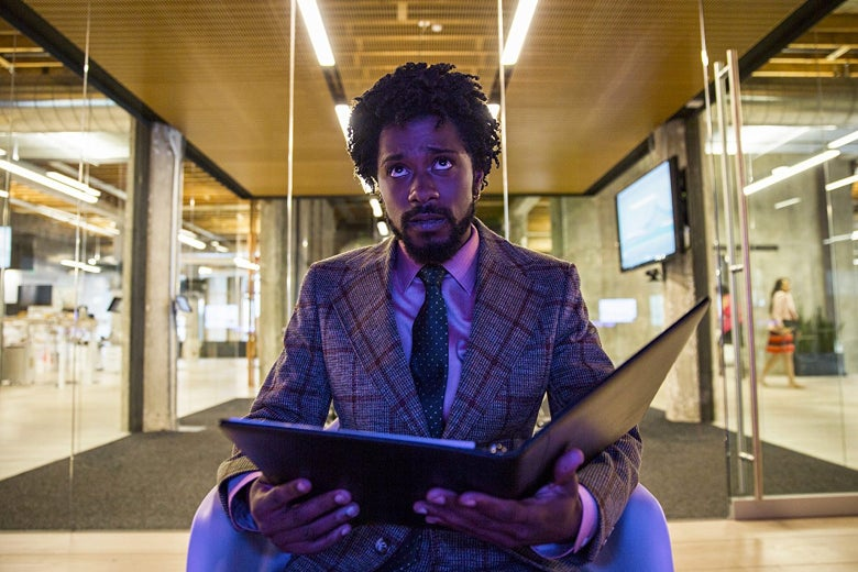 Lakeith Stanfield's character holds open a binder, while in an office setting.