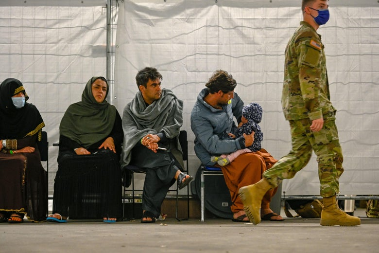 Two women in headscarves and two men, one holding a child in his lap, sit in folding chairs as a man in military fatigues and a mask walks by.