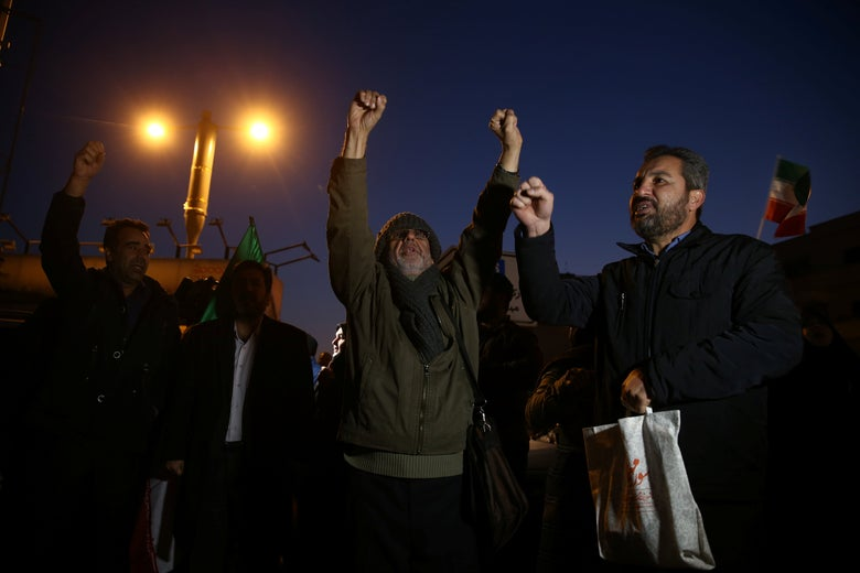 A group of men raise their fists and cheer. An Iranian flag flies in the background.