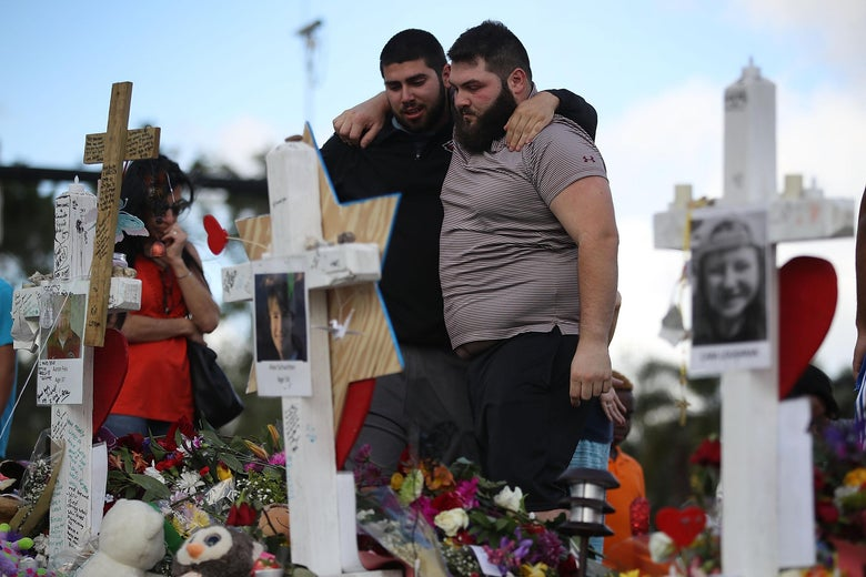 Max Bromberg hugs his brother Samuel Bromberg as they visit a makeshift memorial on February 19, 2018 in Parkland, Florida.