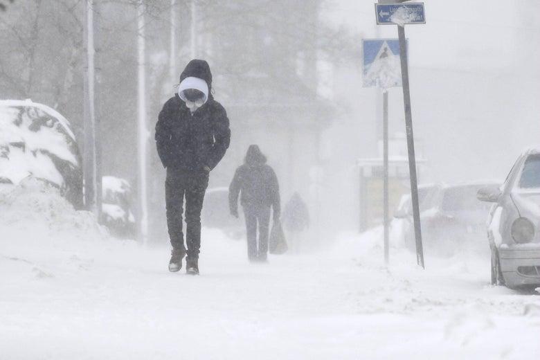 A man walking alone through a blizzard.
