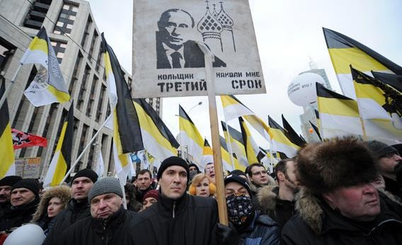 Protesters, activists of nationalist groups, hold the Russian Empire's black-yellow-white flags and a poster depicting Russia's Prime Minister Vladimir Putin.