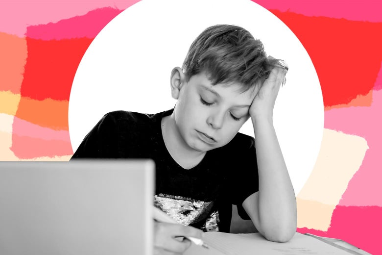 A boy sitting in front of a laptop, head in hand, leaning over, looking down.