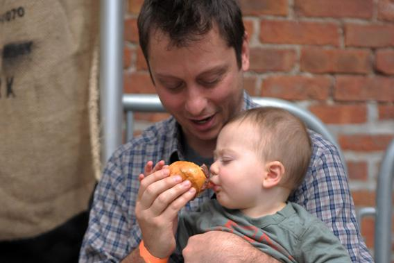 A father feeds his son a burger during the City Harvest Presents The Brooklyn Local at Tobacco Warehouse on September 17, 2011 in New York City.