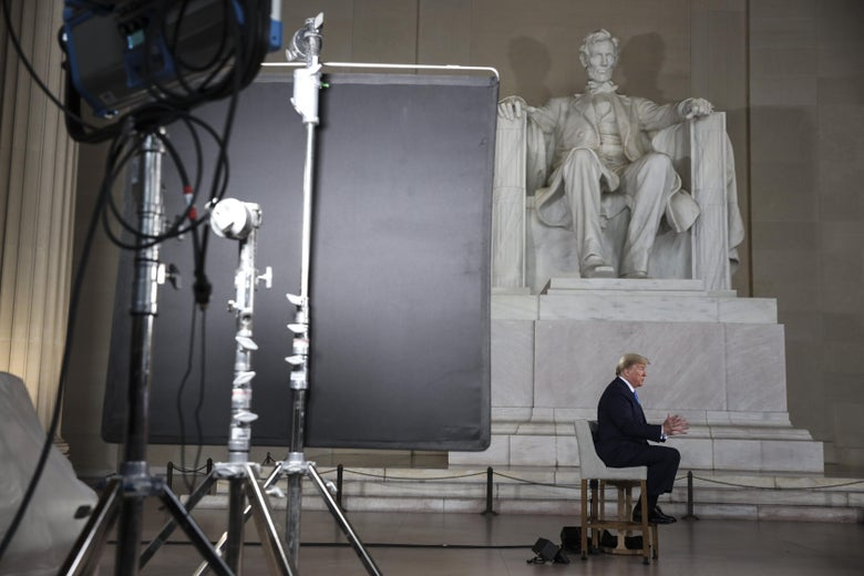 A wide shot of President Donald Trump seated, doing a Fox News town hall in front of the Lincoln Memorial.