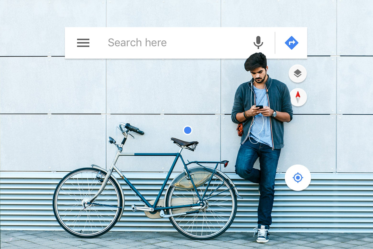 A man on his iPhone standing next to his bicycle.