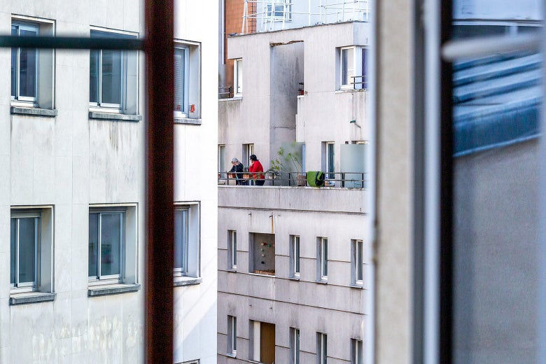 A Paris apartment complex seen out a window, with two people standing on a balcony.
