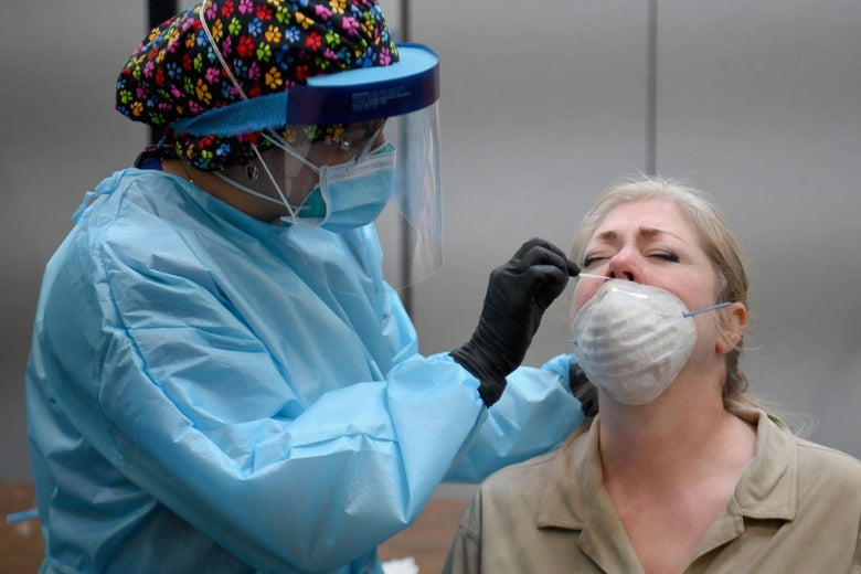 A health care worker puts a nasal swab up a woman's nose