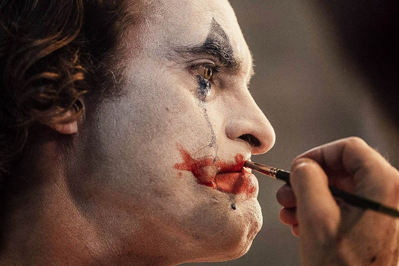 Joaquin Phoenix applies clown makeup to his face in this still from Joker.