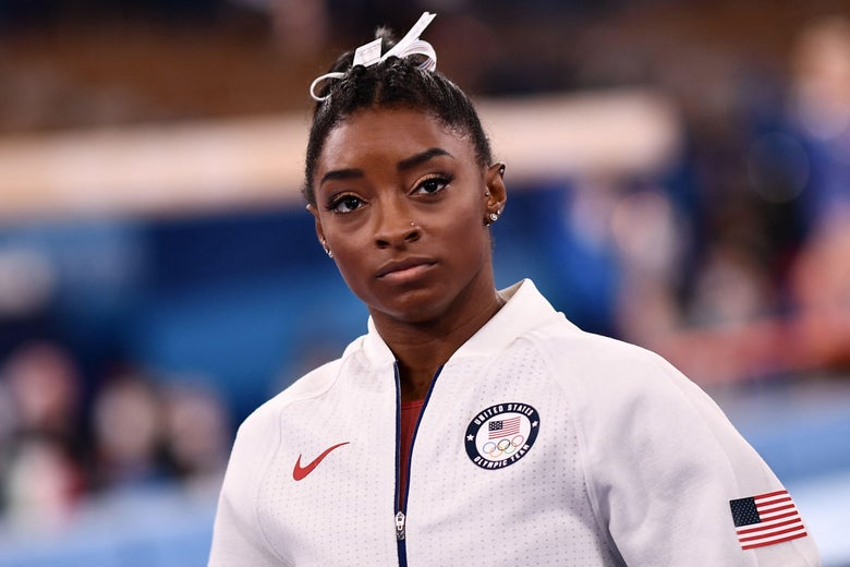 Simone Biles stands on the sidelines during the team final wearing her white USA Olympic warmup suit