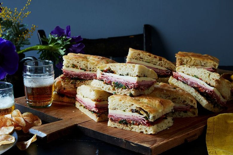 Mortadella sandwiches with provolone cheese on sourdough bread cut into fourths, arranged on a wooden serving board