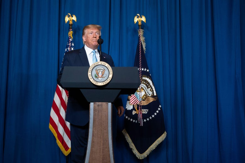Donald Trump speaks at a lectern in front of a blue curtain.