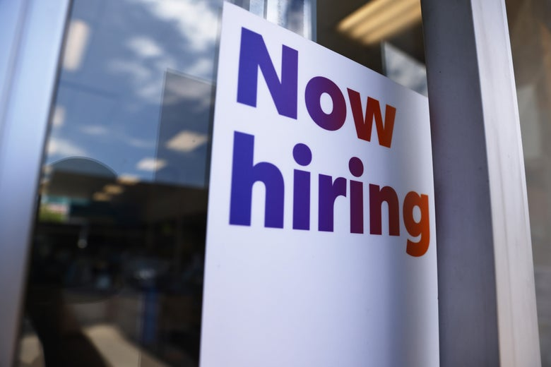 """A """"Now Hiring"""" sign on a storefront"""