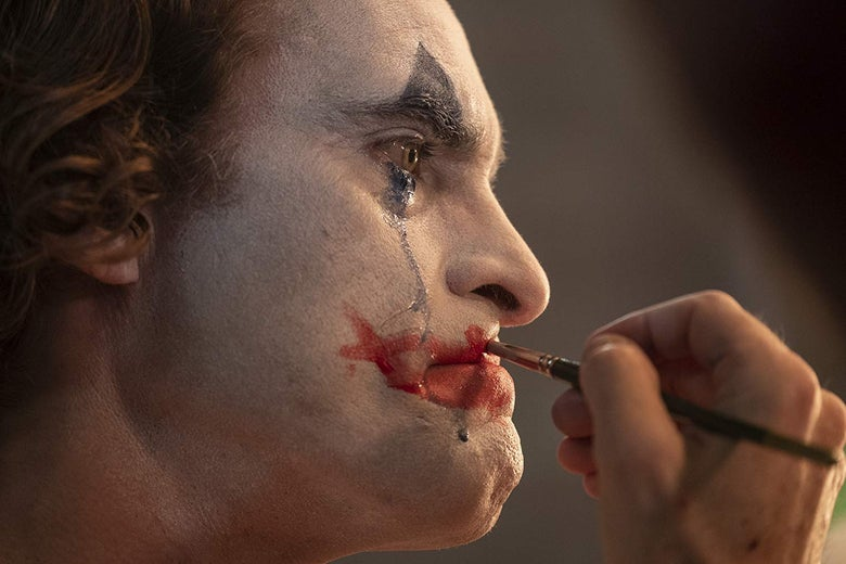 In a close-up, Joaquin Phoenix applies clown makeup to his face. Black eye makeup runs from his eyes down his cheeks.