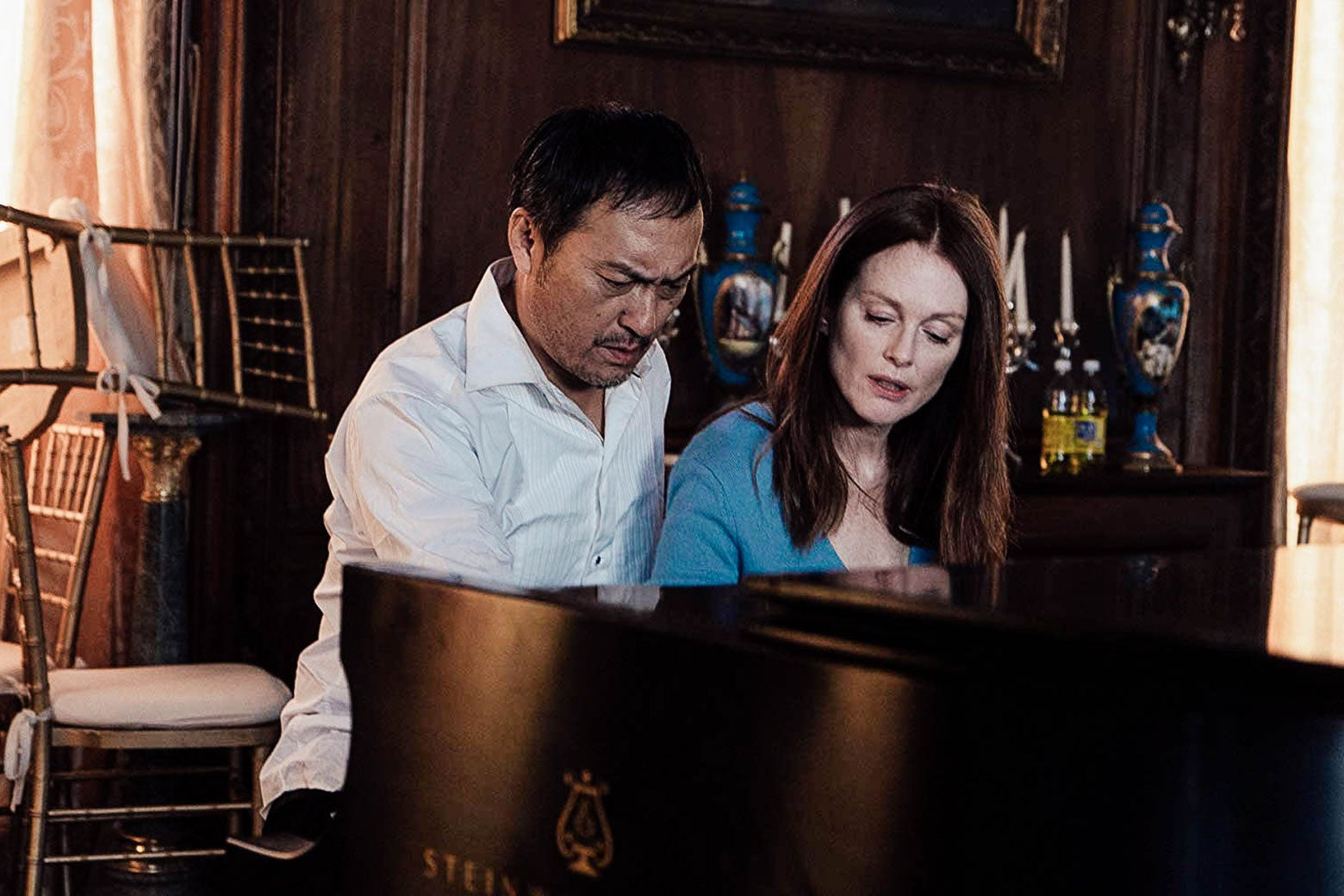 In a scene from Bel Canto, Katsumi Hosokawa, played by Ken Watanabe, and Roxane Coss, played by Julianne Moore, sit at the piano in a richly decorated parlor. Chairs are piled against the window on the left.