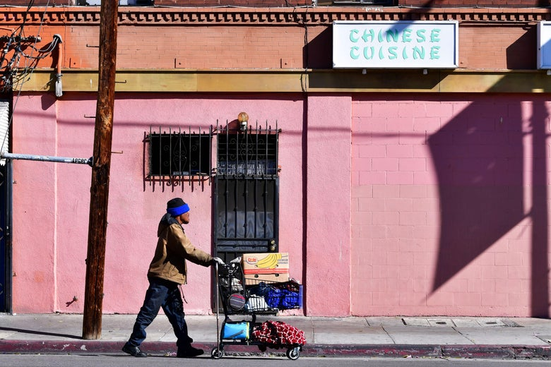 A homeless man pushes a cart full of his belongings along an empty sidewalk