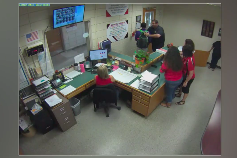 A screen grab from the video of the incident. An officer can be seen putting his hands on a student while others look on in the office.