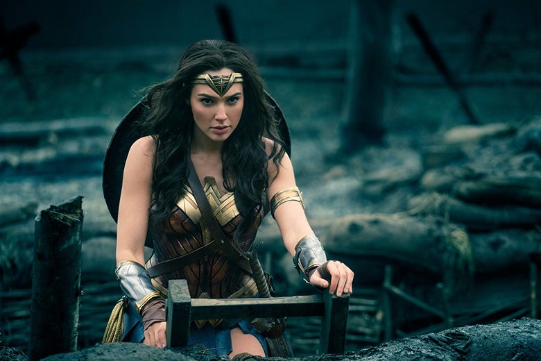 Wonder Woman staring intensely ahead and she stands in the middle of a war zone.