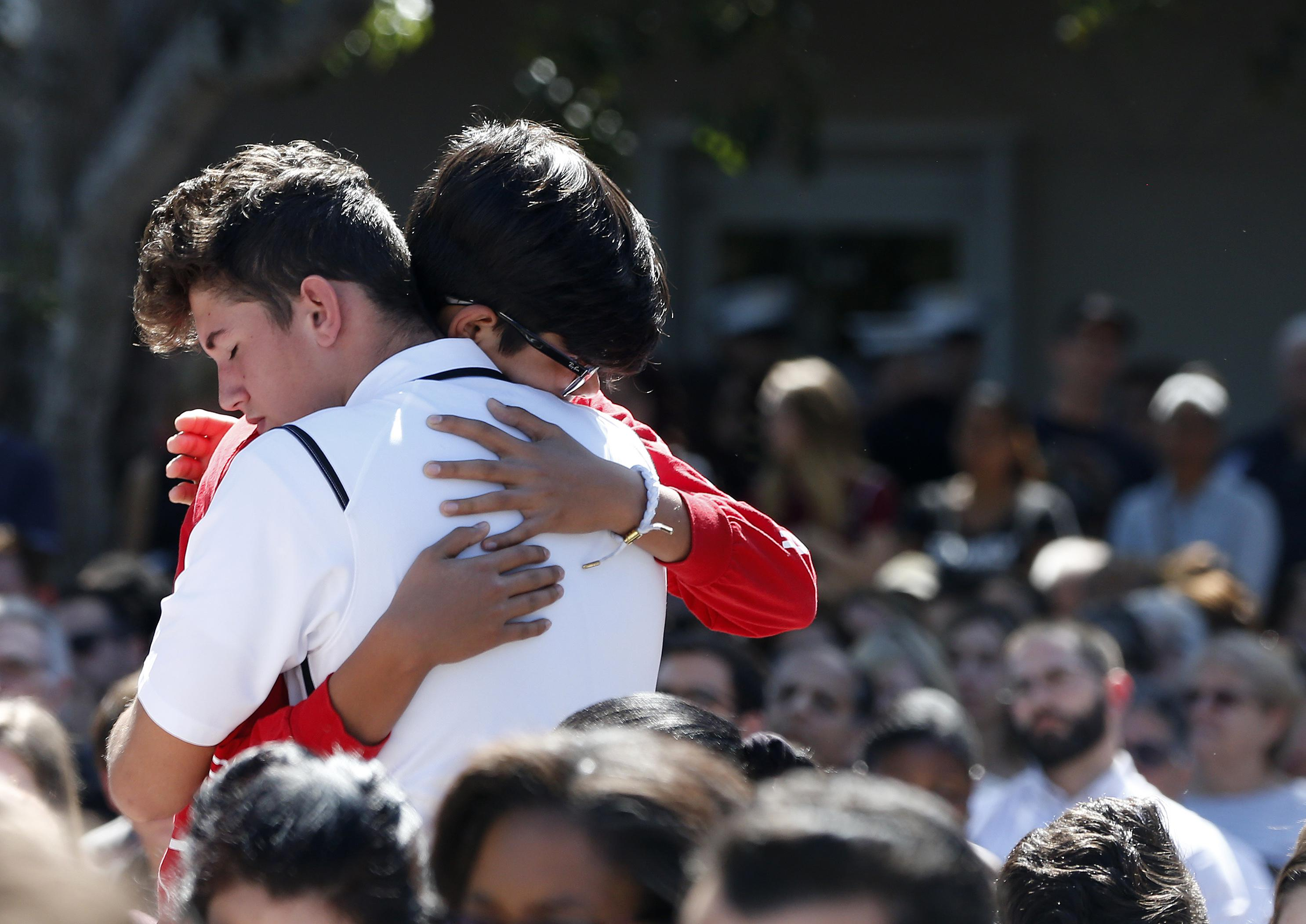 Mourners hug during a prayer vigil for the victims of the Marjory Stoneman Douglas High School shooting at Parkridge Church in Coral Springs, Florida, on Thursday.