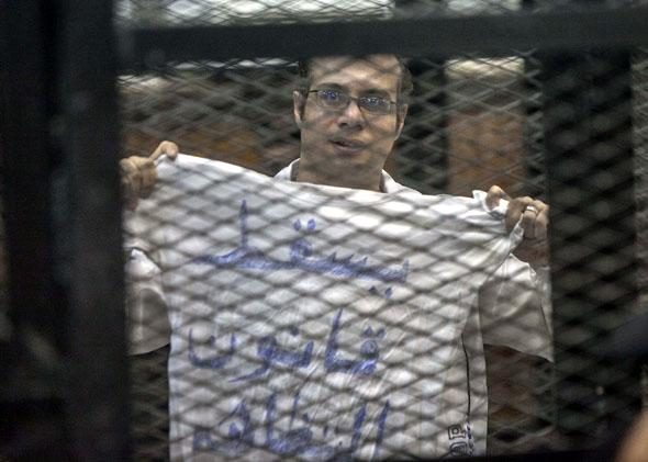 "Political activist and coordinator of the April 6 Movement, Ahmed Maher shows a T-shirt reading ""Dropping the law on demonstrations"" during his trial over an unlicensed and violent demonstration on December 8, 2013 in Cairo, Egypt."