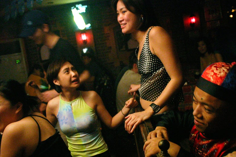 Two women grab each other's hands as they stand in the middle of a crowd in a club.
