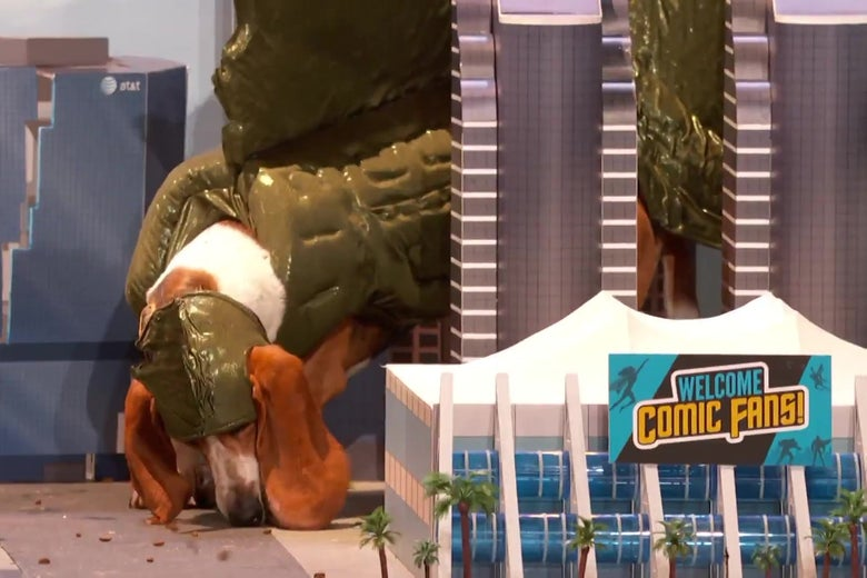 A bassett hound in a Godzilla outfit wanders through a model of San Diego.
