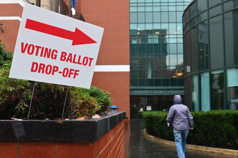 "A person walks in the rain toward a building with a sign out front that says ""Voting Ballot Drop-Off"""