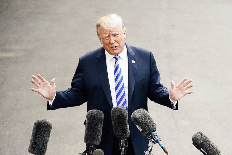 Donald Trump holds his hands up while in front of a bunch of microphones.