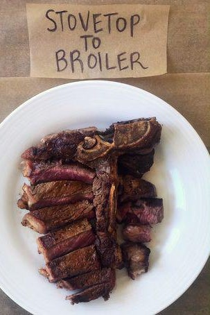 "A T-bone steak on a plate next to a sign labelled ""Stovetop to Broiler."""