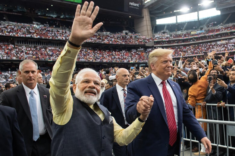 Modi and Trump hold hands as Modi waves at the crowd.