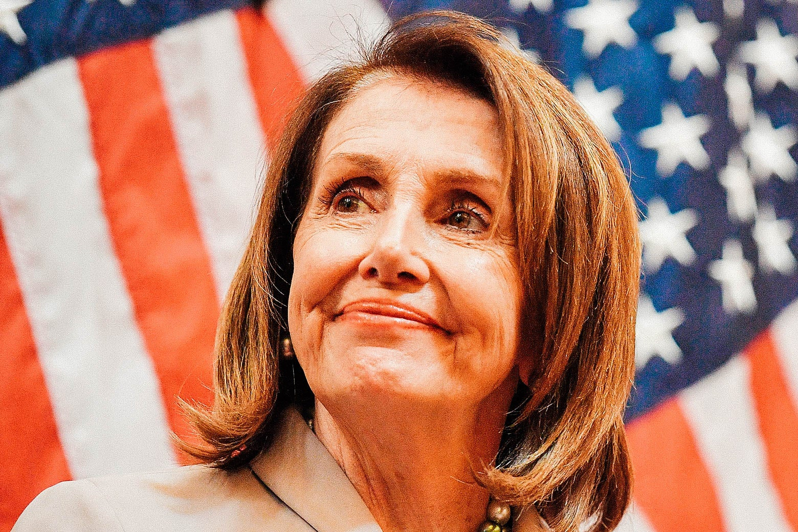 Nancy Pelosi in front of some American flags.
